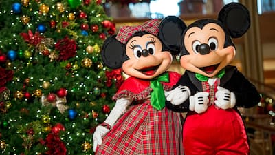 Dressed in holiday attire, Mickey Mouse and Minnie Mouse pose together in front of a Christmas tree