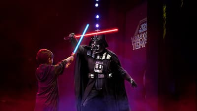 A child dressed as a Jedi warrior engaging in a lightsaber duel with Darth Vadar