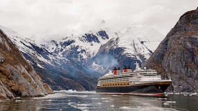 Disney Cruise Line ship emerges from a valley with snow covered mountains