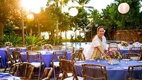 Disney Cast Member sets up outdoor dining tables with floral displays for a reception