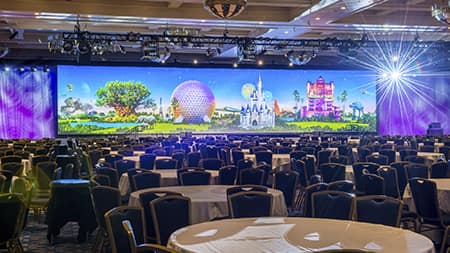 A ballroom filled with round tables and chairs, colorful lighting and monitors
