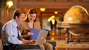 Two attendees looking at a laptop screen inside the lobby of Disneys Yacht Club Resort