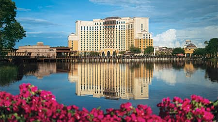 The Gran Destino Tower at Disney's Coronado Springs Resort, adjacent to the waterfront restaurant Villa del Lago, is reflected on the nearby lake
