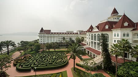 The Hong Kong Disneyland Hotel overlooking a garden maze and the water