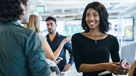 A smiling woman holding her cell phone talks with a man while another man and woman have a discussion in the background