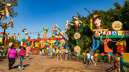 Groups of people walk near the entrance of Toy Story Land
