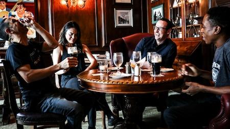 Four friends having fun and drinks at an Irish pub