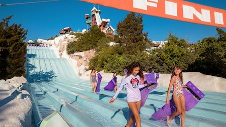 """Dos chicas adolescentes cargando balsas pasan por debajo del letrero """"Finish Line"""" en la parte inferior del tobogán acuático de 8carriles Tobaggan Racers, seguidas de otros Visitantes."""