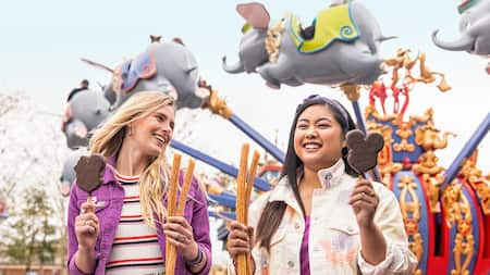 Two ladies hold churros and Mickey premium ice cream bars in front of Dumbo attraction inside Disney's Magic Kingdom park.