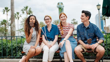 A group of 4 young adults relaxing and eating Mickey ice cream bars at Disneys Hollywood Studios