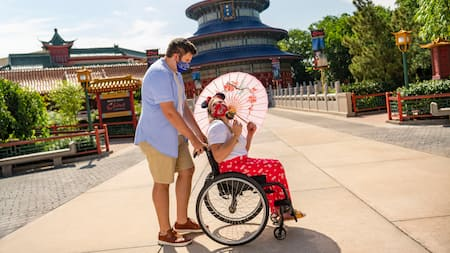 A woman holding an umbrella and seated in a wheelchair while a man pushes her wheelchair at the China Pavilion at Epcot