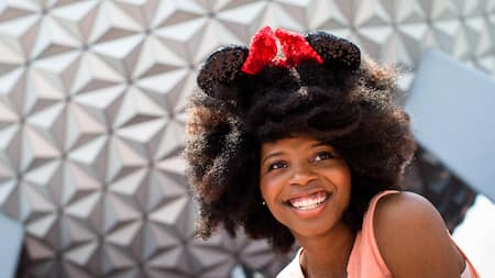 A young woman wearing Mickey ears smiles while standing outside the Epcot Center