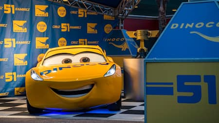 Cruz Ramirez from Cars smiles next to the coveted Piston Cup