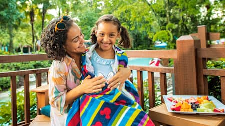 A woman wraps her daughter up in a large beach towel while sitting outside next to a plate of fruit