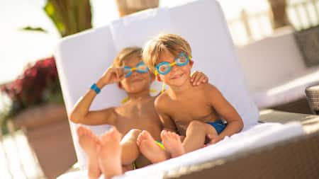 Two little boys wearing swimming goggles sit on a lounge chair