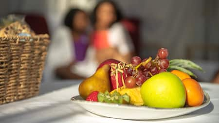 An apple, a pear, grapes and other pieces of fruit on a plate