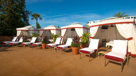 Four cabanas, each with two lounge chairs, lined up on a patio near palm trees