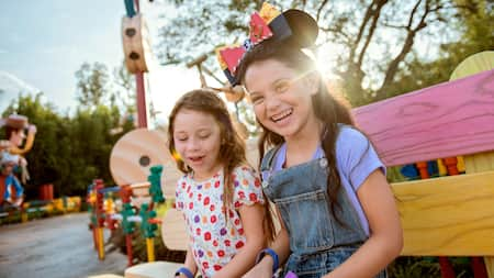 Two girls smiling while sitting on a bench in Toy Story Land