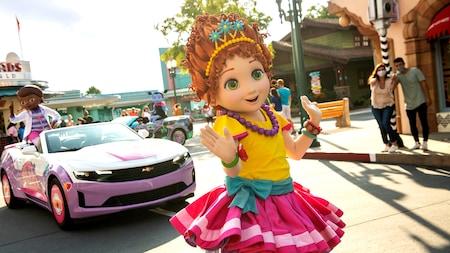 Fancy Nancy saluda mientras camina en el desfile, seguida de carros con Doc McStuffins y Vampirina saludando