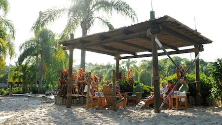 Guests sit on a beach in lounge chairs inside an open-air, wooden shack