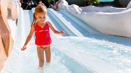 Una niña pequeña sale de un tobogán de agua