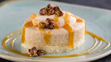 A serving of cheesecake with walnuts and a syrupy topping
