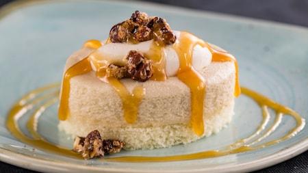 Una porción de cheesecake con nueces y una cobertura de sirope