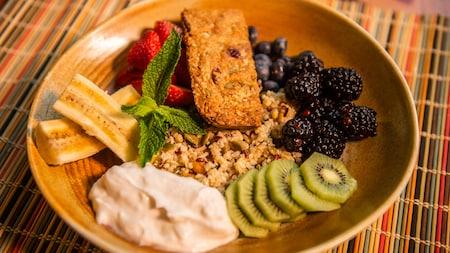 Uma tigela vegetariana com grãos, iogurte, fatias de banana, morango, mirtilo, amora-preta, fatias de kiwi e uma folha de hortelã.