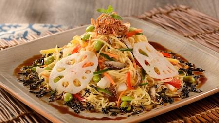 Uma salada vegetariana de macarrão de arroz, edamame, cogumelos, manga verde e pepino em molho de pimenta adocicada.
