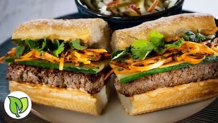 A plant based Banh Mi sandwich roll that includes seasoned vegan meat, shredded carrots, shredded greens and cilantro.