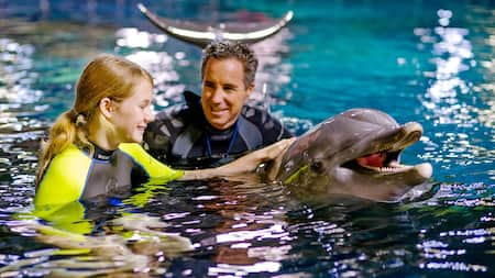 Adult with child petting a dolphin in the water
