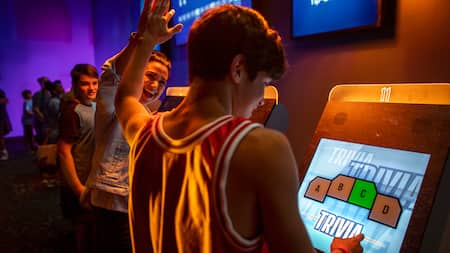 Two Guests high five while playing a touch screen trivia game