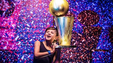 A smiling boy holds up a giant trophy while confetti falls all around him