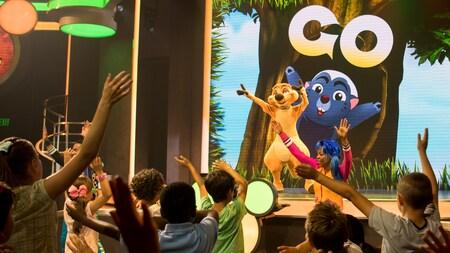 Timon parado en un escenario con sus brazos levantados, frente a un grupo de niños haciéndolos bailar