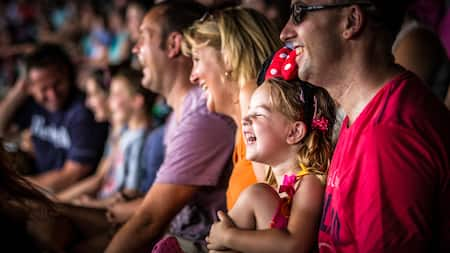 A young girl and her father smile as they watch a show with other Guests