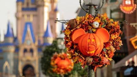 Des couronnes en tête de citrouille Mickey Mouse avec des feuilles et des fleurs sont attachées aux lampadaires