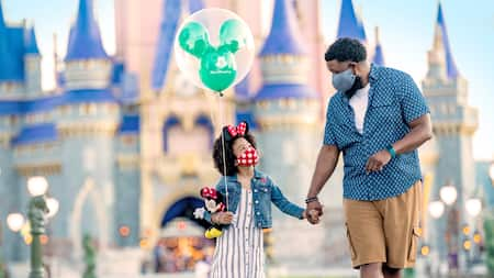 A young girl carrying a balloon and a Minnie Mouse plush while holding her father's hand near Cinderella Castle at Magic Kingdom park