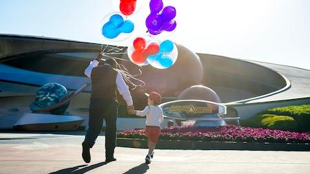 Un guía de excursiones VIP de Disney sostiene globos con temática de Mickey Mouse mientras conduce a un niño hacia Mission Space