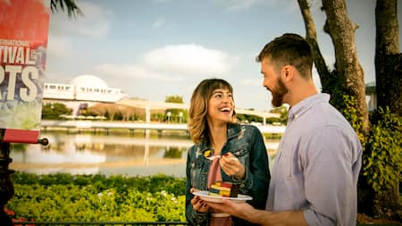 A couple shares a colorful cake in front of the Monorail at Epcot