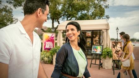 Una pareja pasea frente a tiendas de camping donde se exhibe arte.