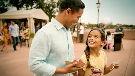 Un Visitante adulto y uno joven comen snacks frente a tiendas de camping con exhibiciones de arte.