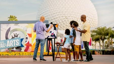 Una familia observa a un artista darle los toques finales a un retrato de Mickey Mouse en Epcot