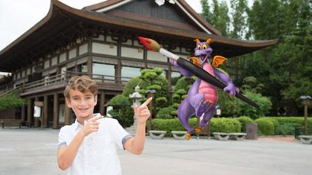 Um menino posando para a foto e apontando para uma imagem em sobreposição do dragão Figment segurando um pincel