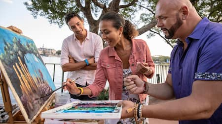 A couple collaborates on an oil painting in an outdoor setting as a Disney artist looks on