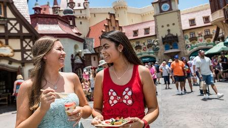 2 jóvenes Visitantes disfrutan snacks y una carcajada frente a Storybook Treats