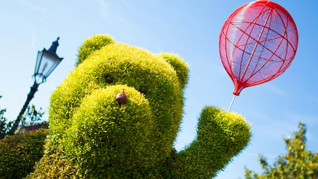 A topiary hedge in the shape of a bear holding a balloon