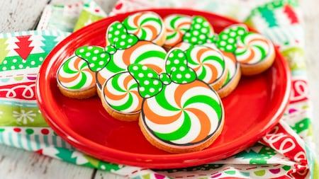 Una bandeja de galletas de azúcar festivas de Minnie Mouse, con forma de orejas y glaseado en un diseño de remolino, junto con un moño de Minnie con lunares