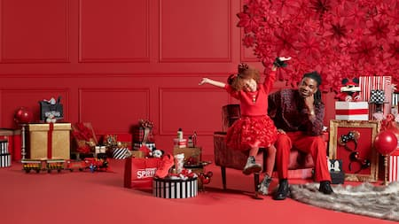 A Dad and his smiling daughter, wearing mouse ears with her arms outstretched, sharing a chair with many holiday gifts on the floor