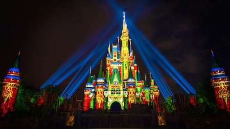 Cinderella Castle dons a festival look with holiday projections and lighting at night in Magic Kingdom Park