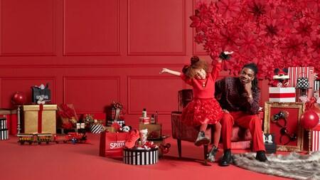 Un padre y su hija sonriente, con orejas de ratón y los brazos extendidos, comparten una silla con muchos regalos navideños en el suelo